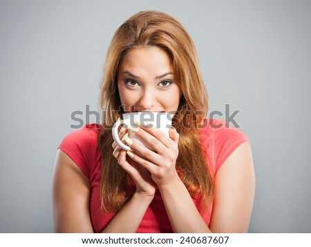 Close-up of beautiful young woman drinking coffee or tea. Studio  shot - stock photo