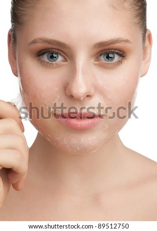Close-up of beautiful young woman removing old damaged skin from her face - stock photo