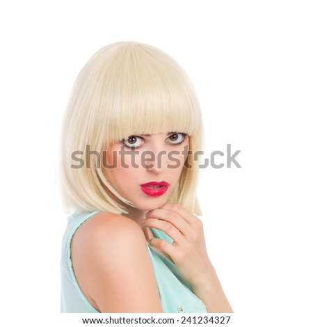 Close up of beautiful young woman with blond fringe looking at camera and holding hand on chin. Head and shoulders studio shot isolated on white. - stock photo