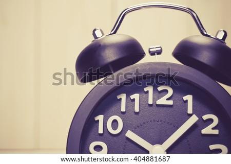 Close up of Black alarm clock  on wood background / vintage tone - stock photo