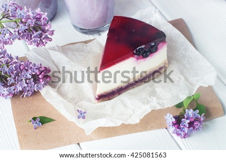 Close up of black current cheesecake slice near bilberry milkshake and lilac flowers on the white wooden background. Selective focus and small depth of field. - stock photo