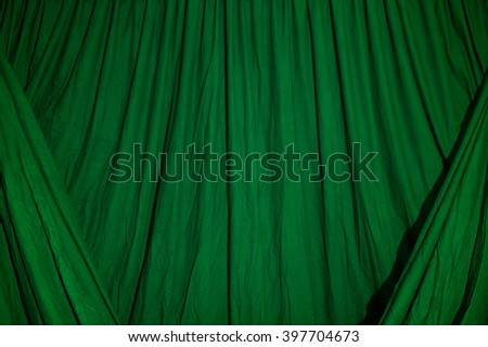 Close up of black draped theatrical curtain or backdrop lit with green gel or filter. - stock photo