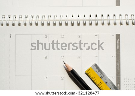 Close up of black sharpened pencil and steel ruler on calendar. - stock photo