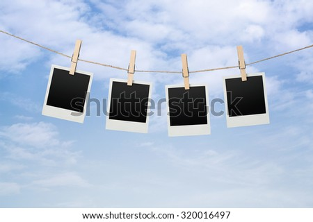 Close up of blank instant photos drying on the clothesline over sky background - stock photo