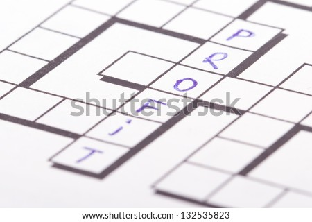Close up of blank square crossword puzzle and profit text. - stock photo