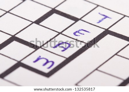 Close up of blank square crossword puzzle and team text. - stock photo