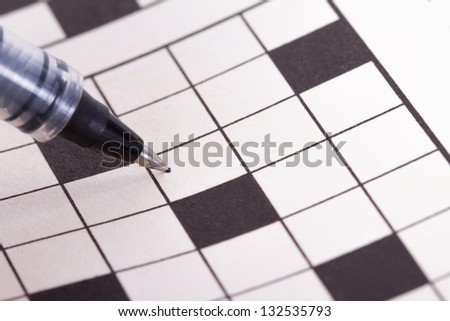 Close up of blank square crossword puzzle for solution with black pen. - stock photo