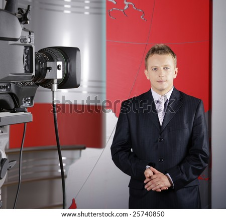 close up of blond middle age television news presenter in studio in front of the camera - stock photo