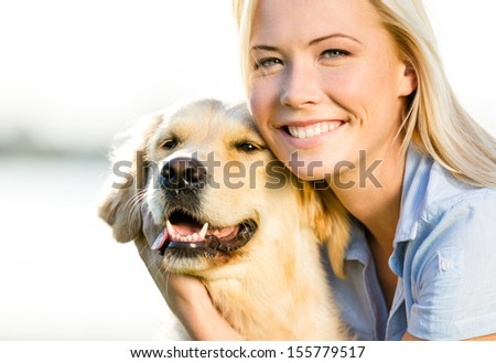Close up of blond woman embracing golden retriever - stock photo