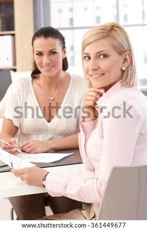 Close up of blonde casual, smiling female worker at business office, looking at camera. - stock photo
