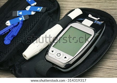 Close up of Blood sugar measurement, Diabetic kit, Syringe pen with insulin and glucometer, Blood glucose test, Blood glucose meter kit. (Vintage Style Color) - stock photo