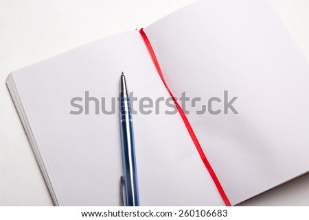 close up of blue pen on blank note book - stock photo