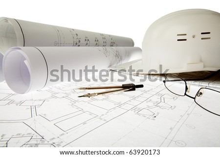 Close-up of blueprints with sketches of projects, helmet, eyeglasses and dividers on them - stock photo