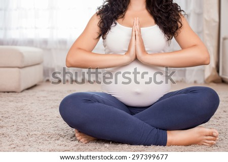 Close up of body of pregnant woman sitting on floor in lotus position. She joined her palms together - stock photo