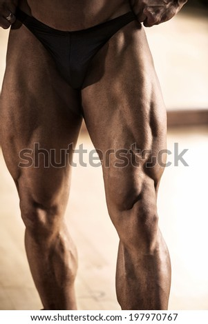 Close-up of bodybuilder showing his muscular thigh - stock photo