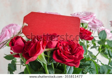 Close-up of bouquet of red roses with red wooden plank on table - stock photo
