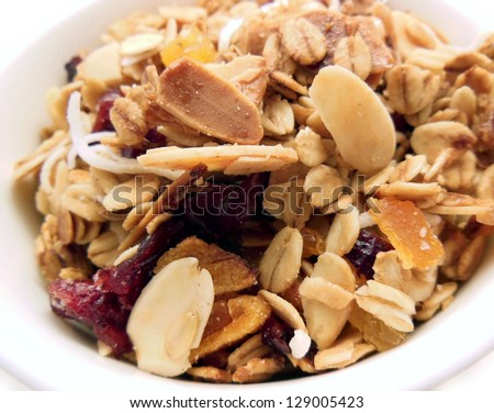 Close-up of bowl full of homemade granola with almonds, oats, cranberries, apricot and coconut. - stock photo