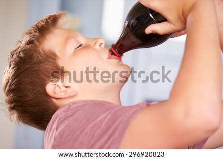 Close Up Of Boy Drinking Soda From Bottle - stock photo