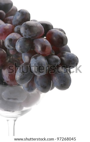 Close-up of branch of purple grape in wineglass on white background. - stock photo