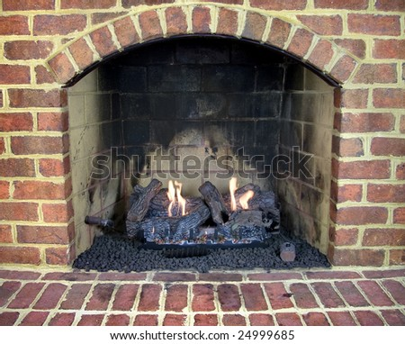 Close up of brick gas fireplace with a lit fire. - stock photo