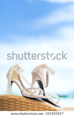 Close-up of bridal shoes with crystal necklace. Shallow depth of field. - stock photo