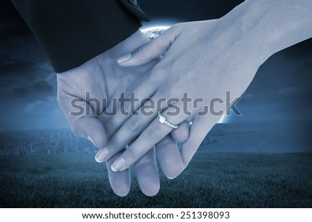 Close-up of bride and groom with hands together against bright moon over city - stock photo
