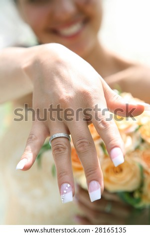 Close-up of bride?s hand with posh wedding ring showing it to you - stock photo