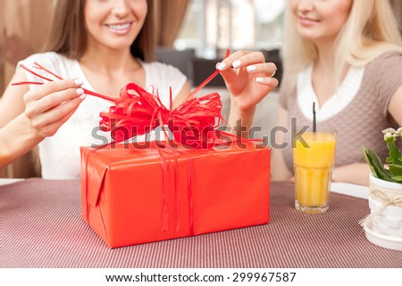 Close up of bright red box of a gift. Cheerful women are sitting in cafe with joy. The brunette lady is opening her gift and smiling - stock photo