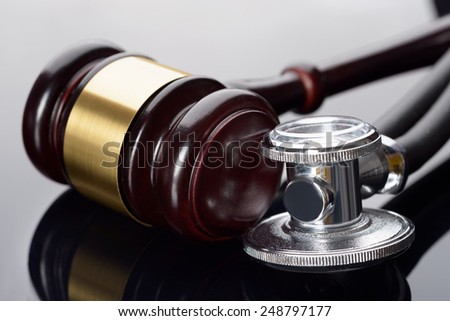 Close-up Of Brown Gavel And Medical Stethoscope - stock photo