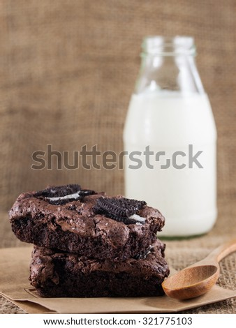 Close up of brownie with cookies topping, milk and wooden spoon in the blurred background, selective focus - stock photo