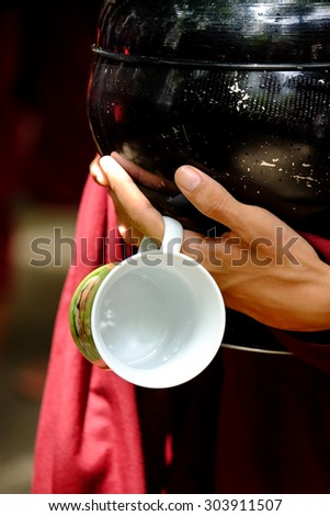 Close up of buddhist monk hands holding a vintage bowl and cup - stock photo
