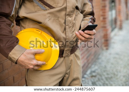 Close-up Of Builder Holding Hardhat And Using Cellphone - stock photo