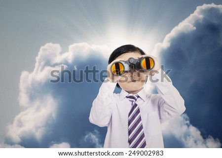 Close-up of business boy holding binoculars under cloudy sky - stock photo