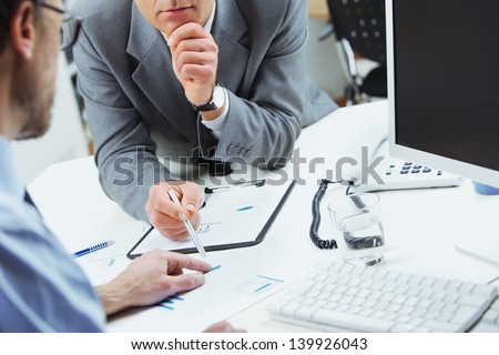 Close up of business colleagues discussing together in an office - stock photo