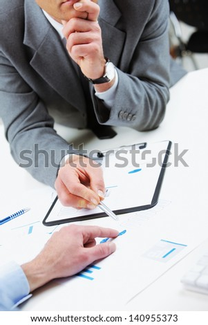 Close up of business colleagues discussing together in an office, hands close up - stock photo