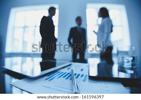 Close-up of business document and touchpads at workplace on background of office workers interacting - stock photo