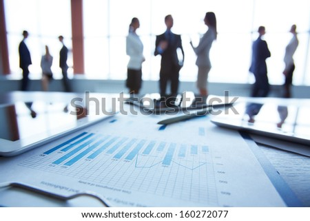 Close-up of business document in clipboard at workplace on background of office workers interacting - stock photo