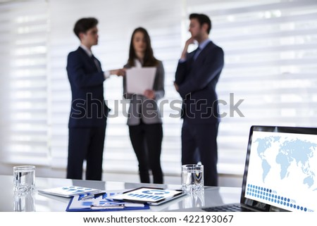 Close-up of business document in touch-pad lying on the desk, office workers interacting in the background - stock photo