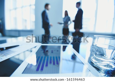 Close-up of business document in touchpad at workplace on background of office workers interacting - stock photo