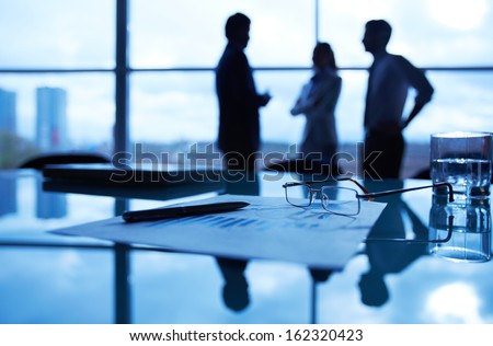 Close-up of business document, pen, glass of water and eyeglasses at workplace on background of office workers interacting - stock photo