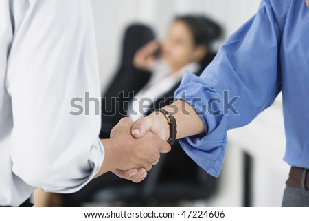 Close up of business executives shaking hands. - stock photo