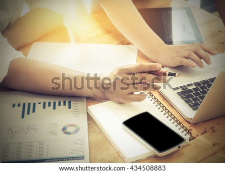 Close-up of business female and male hands using pen and pointing at turnover graph while discussing it on wooden desk in office with morning light, Vintage concept. - stock photo