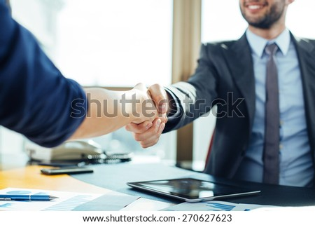 Close up of business handshake in the office - stock photo