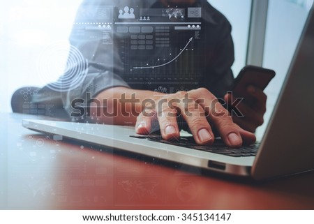 Close up of business man hand working on laptop computer with digital business strategy diagram on wooden desk as concept - stock photo