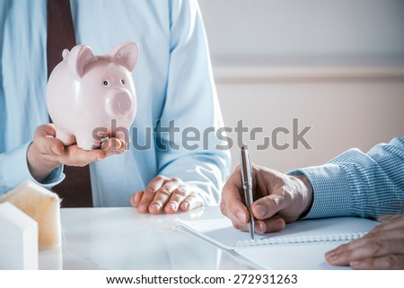 Close Up of Business Man Holding Pink Piggy Bank in Meeting with Co-Worker Taking Notes in Note Book, Real Estate or Investment Concept Image - stock photo