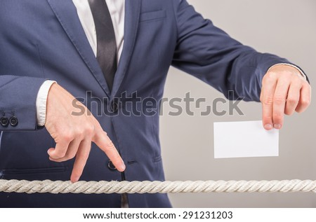 Close-up of business man's hand walking with fingers on rope and holding business card in another hand. - stock photo