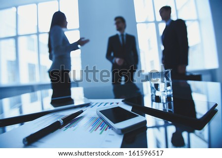 Close-up of business objects at workplace on background of office workers interacting - stock photo