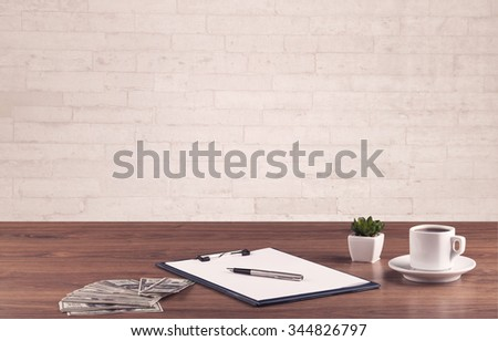 Close up of business office desk with pen board coffee in front of empty white brick textured wall background. - stock photo