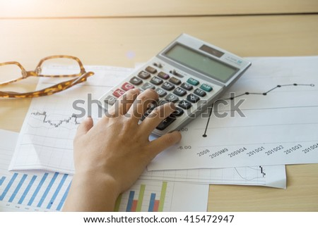 Close up of Business people counting on calculator sitting at the table. Close up of hands and stationery - stock photo
