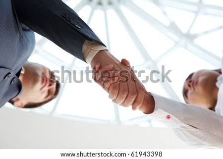 Close-up of business people handshaking above camera - stock photo